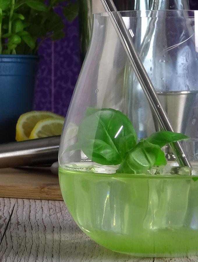 Rezept für selbstgemachten Gin Basil Smash mit Bombay Sappphire London Dry Gin, Basilikum, Zuckersirup, Zitronensaft und Eiswürfeln. Nahaufnahme i, Gin Tumbler.