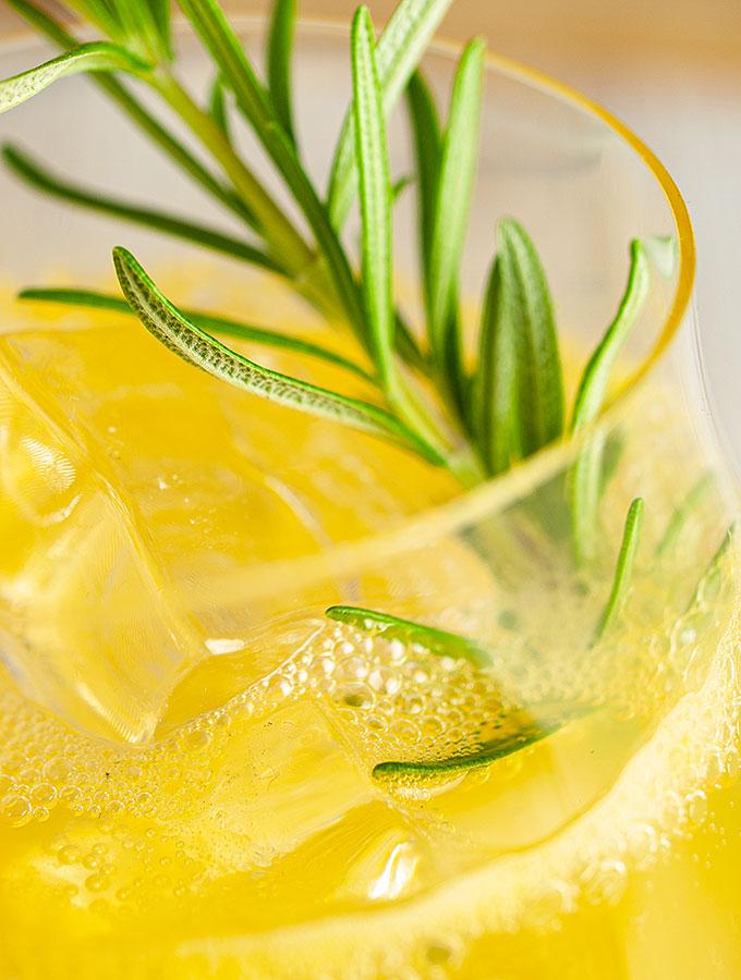 Im Smoky Bombay Twist finden rauchiger Single Malt Scotch Whisky und aromatisch komplexer London Dry Gin zusammen. Nahaufnahme Smoky Bombay Twist im Gin Tumbler mit Eiswürfeln und Rosmarinzweig.