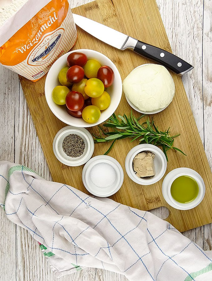 Die Zutaten für klassisches italienisches Tomaten-Foccacia: Mehl, Kirschtomaten, Wasser, Olivenöl, Rosmarin, Hefe, Mozzarella, Chili, Salz Pfeffer