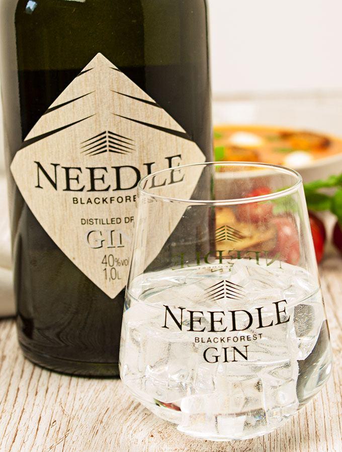 Ein Glas Blackforest Needle Gin sowie eine Flasche des Needle Gins. Im Hintergrund die Tomatensuppe mit Schwarzwald Gin der Bimmerle KG Private Distillery in weißem Suppenteller, rote Kirschtomaten, geröstete Rosmarin-Knoblauch-Baguettescheiben sowie weiteres Geschirr.