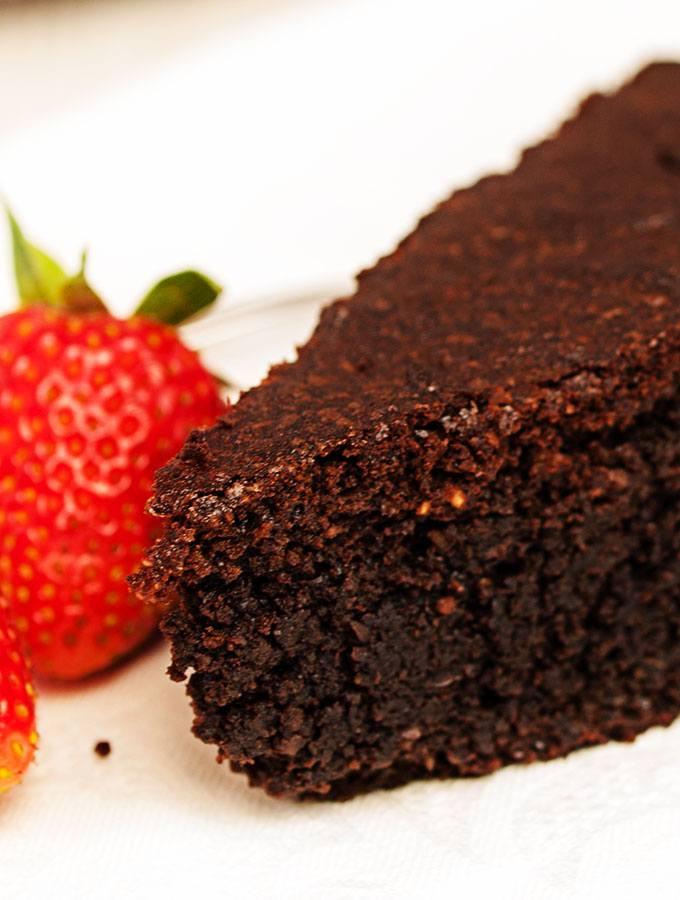 Ein Stück Brownie-like Schokoladenkuchen in der Nahansicht, dekoriert mit frischen Erdbeeren und roten Johannisbeeren