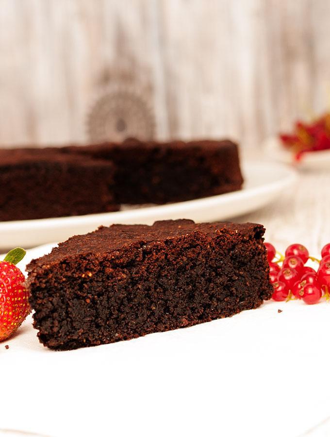 Ein Stück Brownie-like Schokoladenkuchen in der Frontalansicht, dekoriert mit frischen Erdbeeren und roten Johannisbeeren. Im Hintergrund ist der ganze Schokoladen auf einer weißen Kuchenplatte zu sehen.