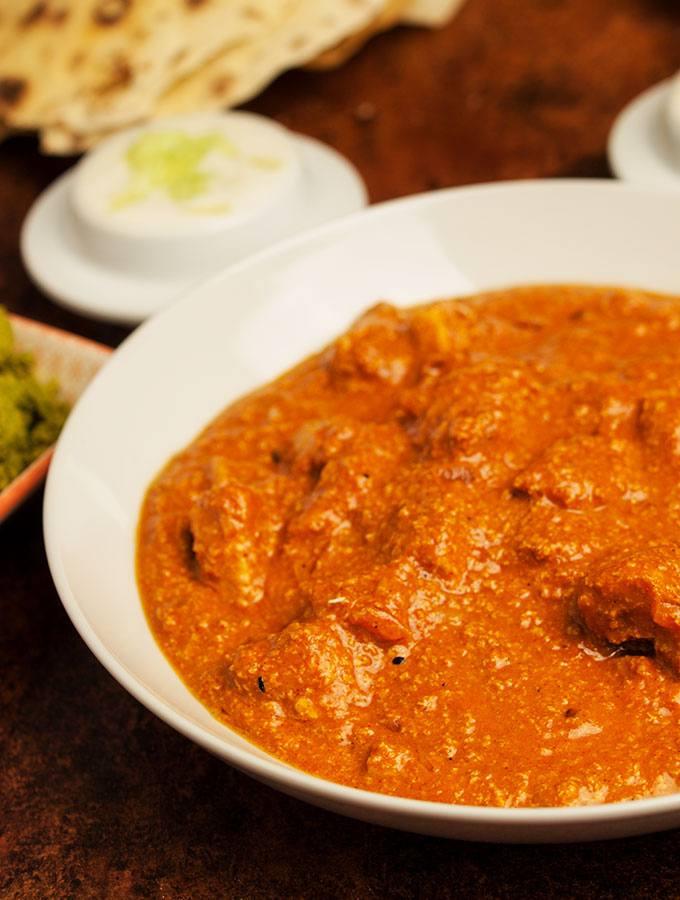 Butter Chicken Curry (Chicken Makhani, Murgh Makhani) in weißer Schüssel. Im Hintergrund in diversen Schüsselchen: grünes Kokosnuss-Chutney, rotes Chutney, Chapati, P, Gurken-Raita und Tomaten-Raita.