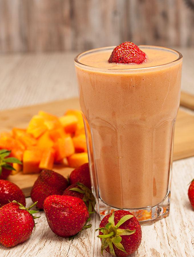 Magenschonender Erdbeer-Papaya-Smoothie in großem Glas,fotografiert in Frontalansicht. Als Dekoration im Hintergrund Erdbeeren und Papaya-Stückchen.