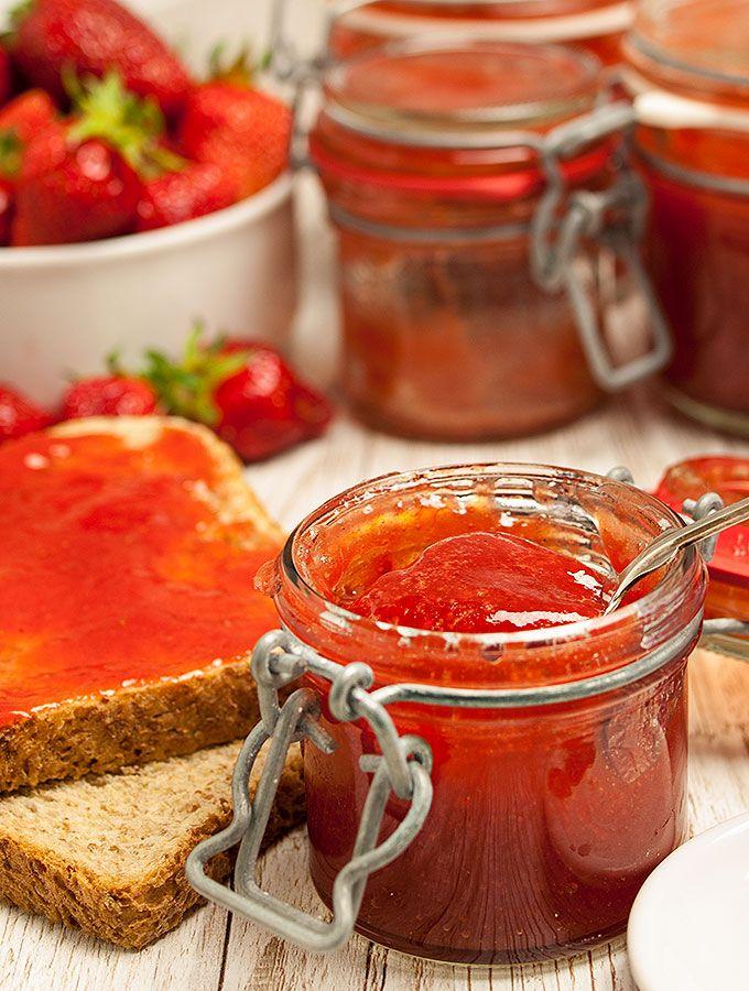Erdbeer-Rhabarber-Marmelade im 125-ml-Einmachglas mit ein wenig Marmelade auf einem Silberlöffel. Im Hintergrund frische Erdbeeren in einer weißen Porzellanschale, zwei Scheiben Toast und mehrere Einmachgläser, ebenfalls gefüllt mit Erdbeer-Rhabarber-Marmelade.