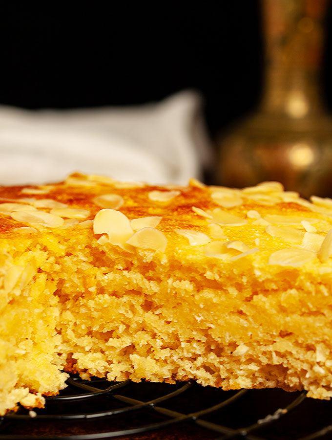 Rezept für Harissa, einen tradtionellen arabischen Kuchen aus Joghurt, Grieß und Kokosflocken und Zuckersirup. Perfekt auch als Dessertkuchen. Angeschnittener Harissa auf Kuchengitter in der Nahaufnahme.