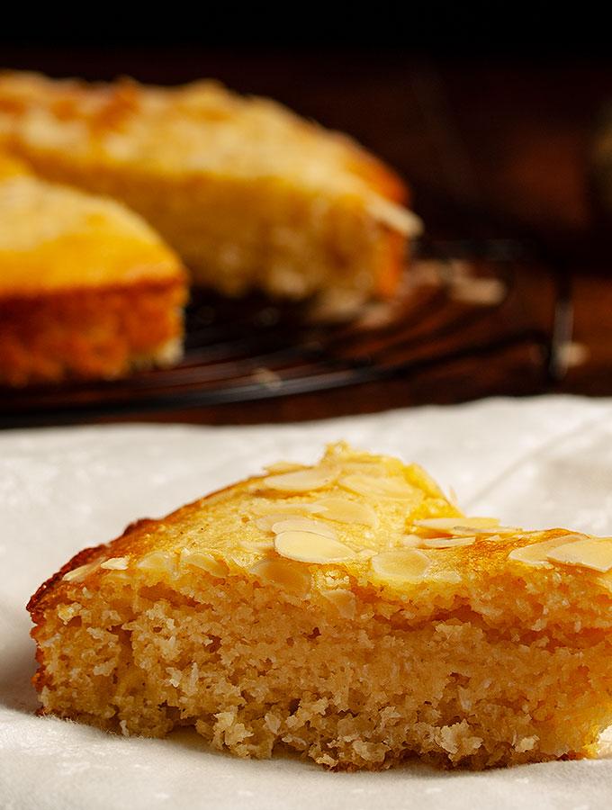 Rezept für Harissa, einen tradtionellen arabischen Kuchen aus Joghurt, Grieß und Kokosflocken und Zuckersirup. Perfekt auch als Dessertkuchen. Ein Stück Harissa in der Nahaufnahme.