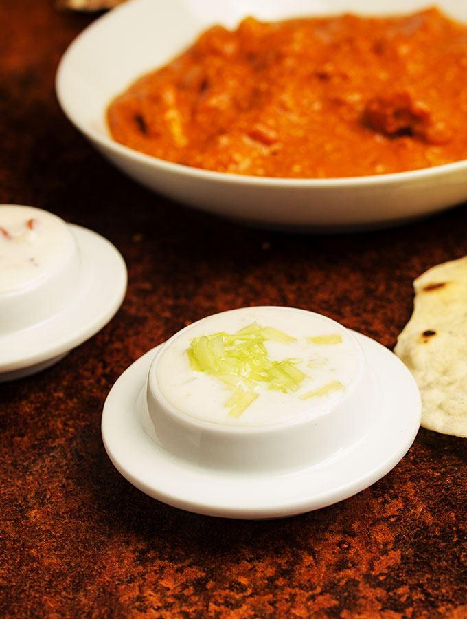 Indisches Gurken-Raita in kleinem, weißen Beilagenschälchen. Im Hintergrund rotes Kokosunss-Chutney, Butter Chicken Curry und Chapati.