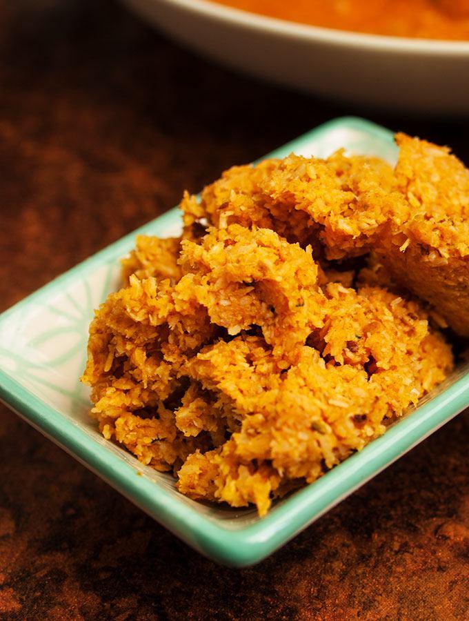 Indisches Grünes Kokosnuss-Chutney in kleinem Porzellan-Schälchen. Im Hintergrund eine Schüssel indisches Butter Chicken Curry, Tomaten-Raita und indisches Fladenbrot Chapati.