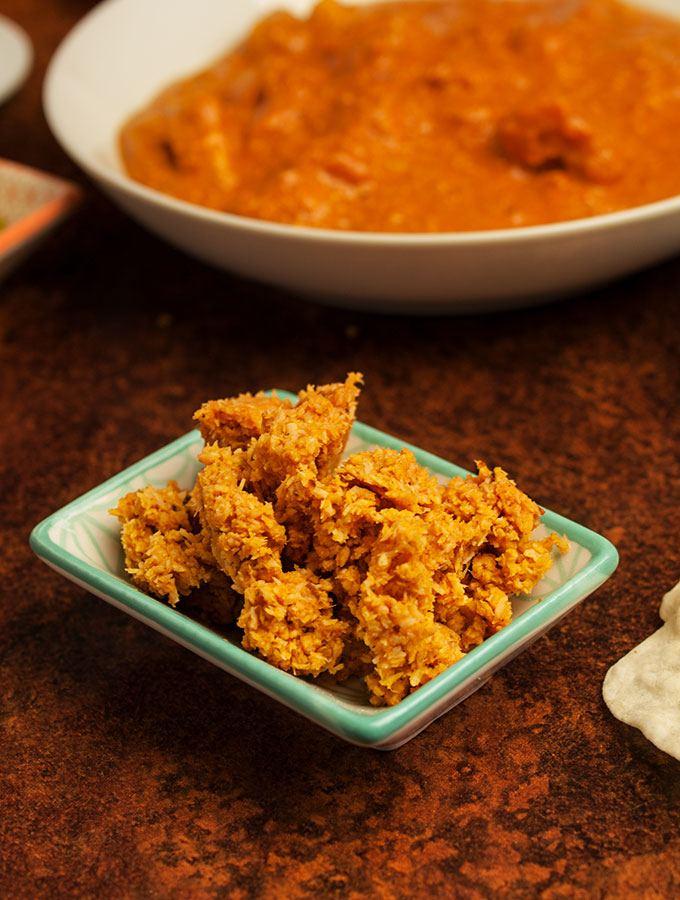 Indisches Rotes Kokosnuss-Chutney in kleinem Porzellan-Schälchen. Im Hintergrund eine Schüssel indisches Butter Chicken Curry, Tomaten-Raita und indisches Fladenbrot Chapati.