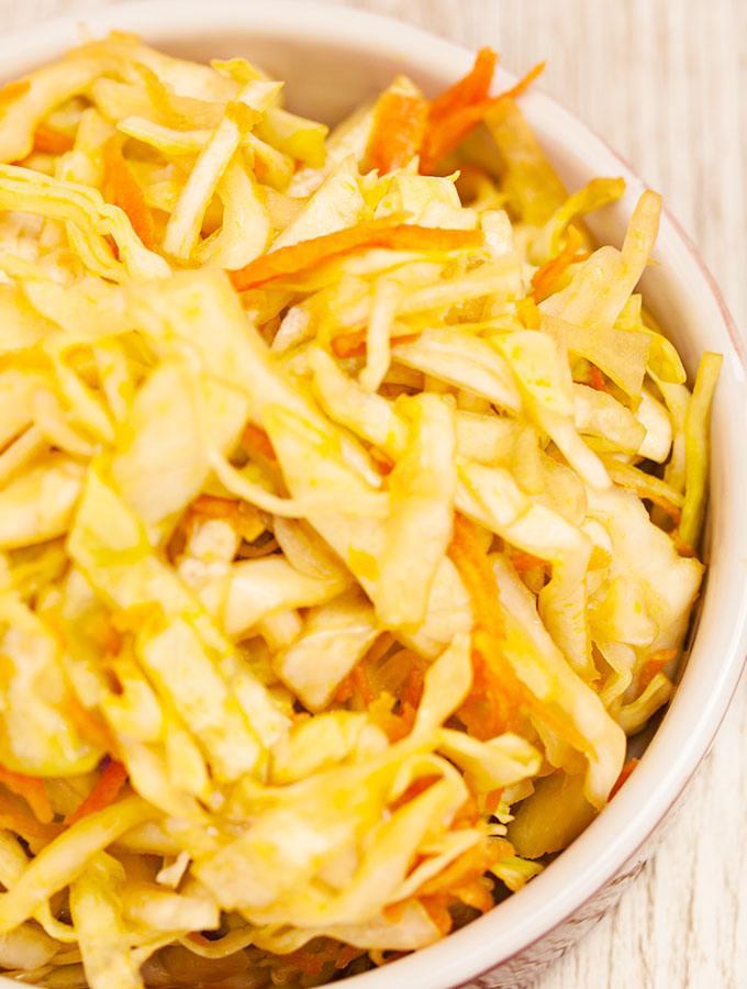 Süß-scharfer Krautsalat in weinroter Schüssel. Fotografiert als Nahaufnahme.