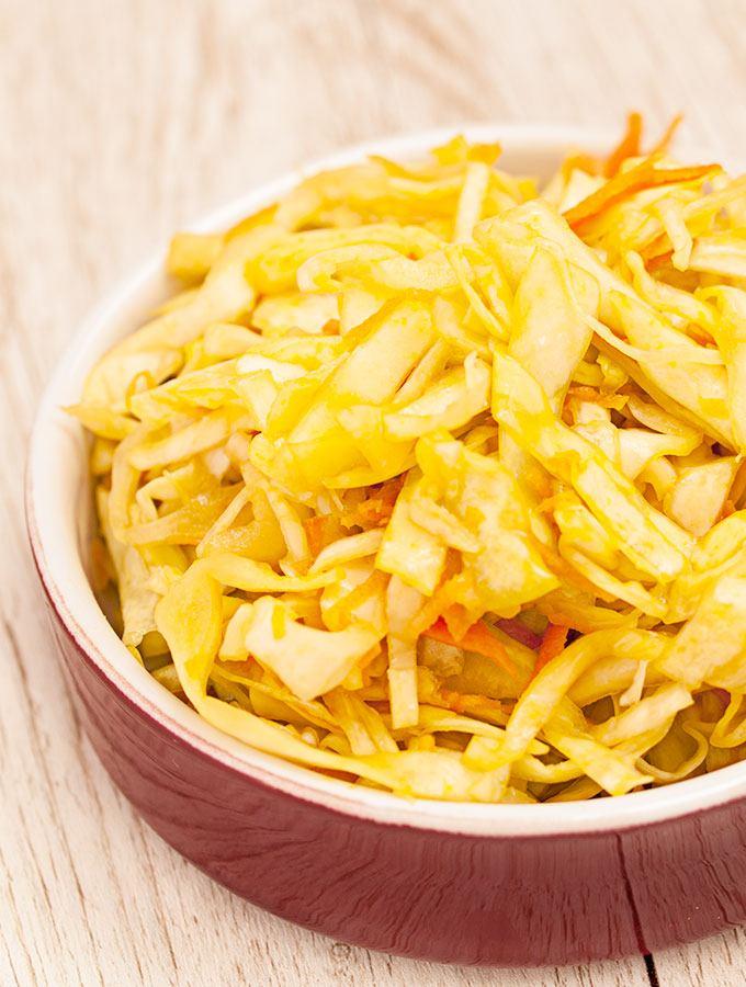 Süß-scharfer Krautsalat in weinroter Schüssel. Fotografiert als Frontalaufnahme.
