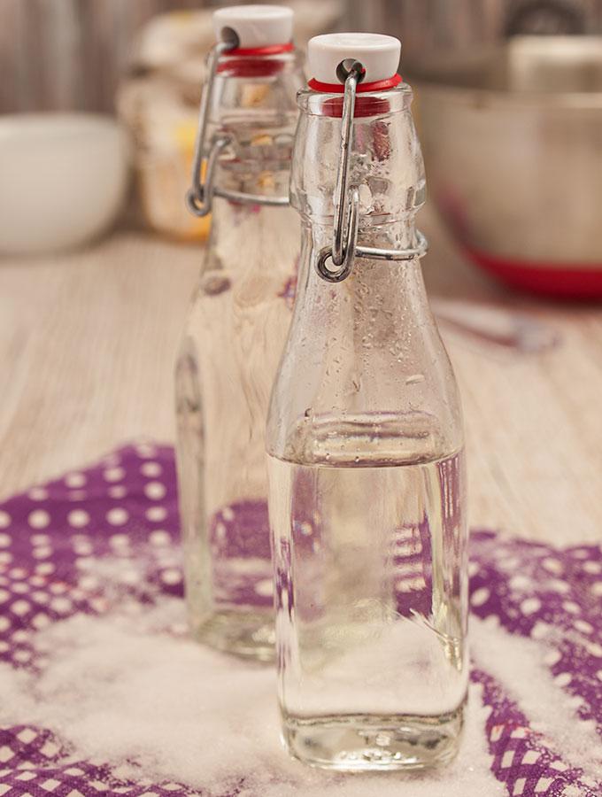 Zwei Einmachflaschen Läuterzucker (Zuckersirup) auf lila-weißem Geschirrtuch, fotografiert in Frontalaufnahme. Im Hintergrund diverse Backzutaten.