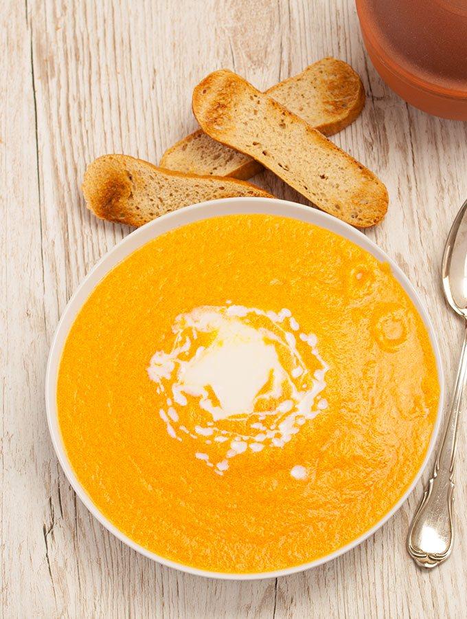 Lauwarme Karotten-Ingwer-Suppe in weißem Suppenteller. Fotografiert aus der Vogelperspektive. Als Dekorationen dienen ein paar angeröstete Scheiben Weißbrot und ein silberner Suppenlöffel.