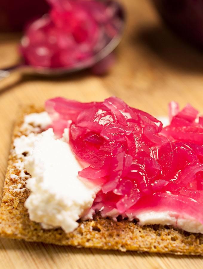 Pinke Zwiebeln auf Roggen-Knäckebrot mit Quark. Im Hintergrund Einmachgläser mit pinken Zwiebeln, mehrere Scheiben Roggen-Knäckebrot und rote Zwiebeln.