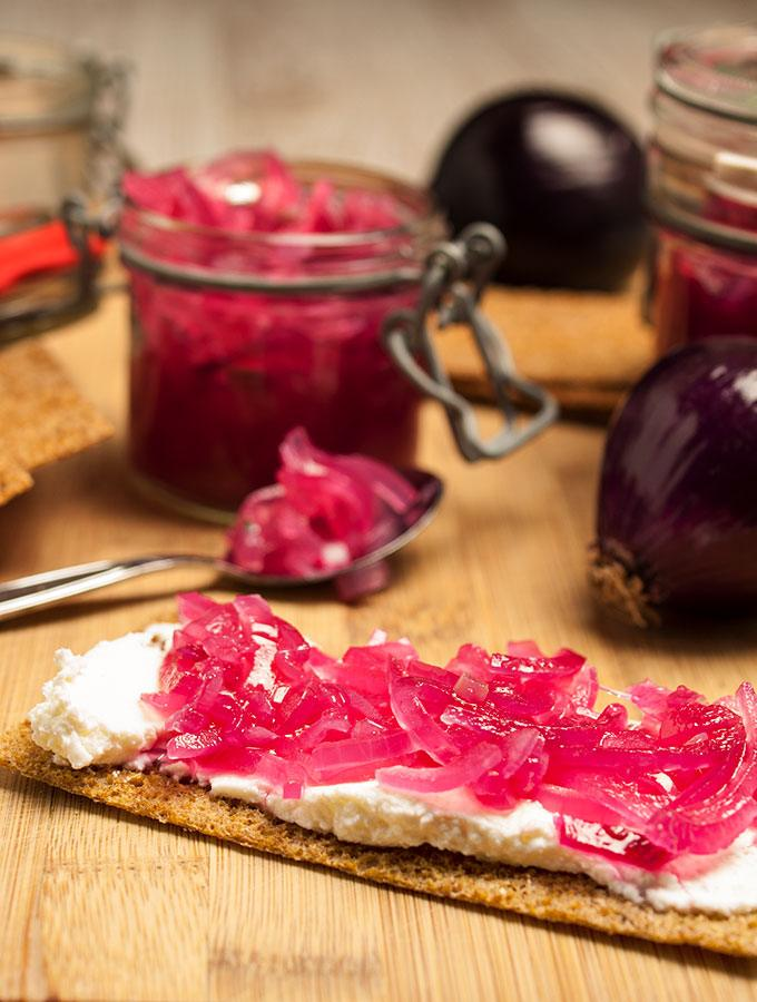 Pinke Zwiebeln Roggen-Knäckebrot mit Quark. Im Hintergrund Einmachgläser mit pinken Zwiebeln, mehrere Scheiben Roggen-Knäckebrot und rote Zwiebeln.