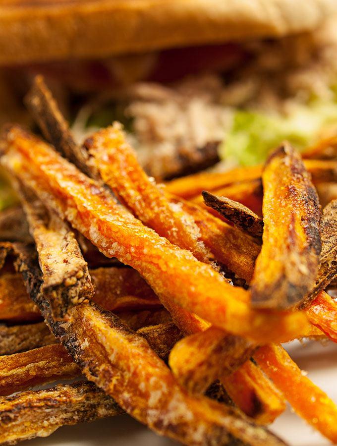 selbstgemachte Süßkartoffel-Pommes frites in der Nahaufnahme. Im Hintergrund ein Pulled Chicken Sandwich.
