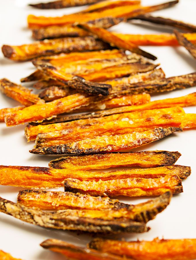 selbstgemachte Süßkartoffel-Pommes frites auf weißem Teller, nacheinander aufgereiht.