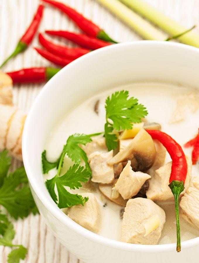 Thailändische Kokosnuss-Hühnersuppe Tom Kha Kai (Tom Kha Gai) in weißer Suppenschüsselmit roter Chili und Korianderblättern. Als Dekorationen dienen einige Stangen Zitronengras, Galgant und Chilis. Fotografiert als Nahaufnahme in der Halbtotalen.
