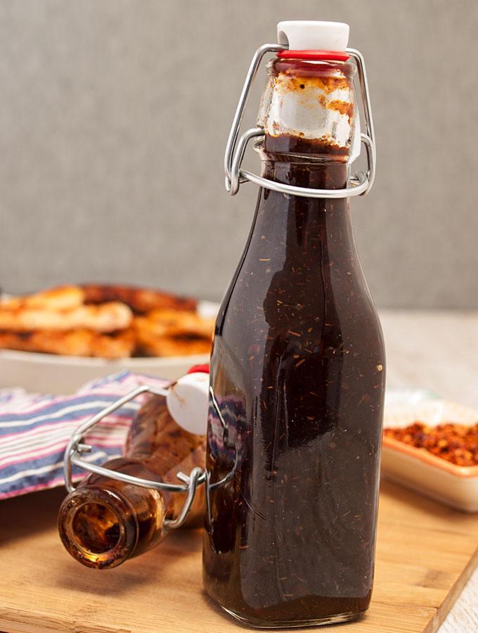 Whisky-Chili-BBQ-Sauce mit rauchigem schottischem Whisky und einer leichten Chili-Schärfe in einer verschließbaren, klaren Bügel-Glasflasche in Fronatlaufnahme. Im Hintergrund eine umgekippte, bereits Flasche Whisky-Chili-BBQ-Sauce, eine Teller mit Grillfleisch.