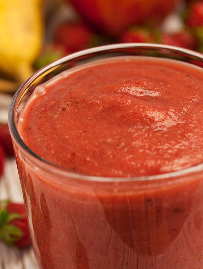 Erdbeer-Power-Smoothie im Glas, fotografiert als Nahaufnahme. Als Dekorationen dienen Erdbeeren und Bananen.