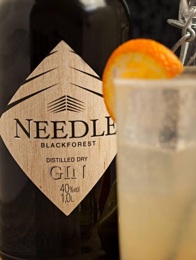 Im Vordergrund Longdrink-Glas Tom Collins mit einer Orangenscheibe. Im Hintergrund eine Flasche Needle Blackforest Dry Gin.