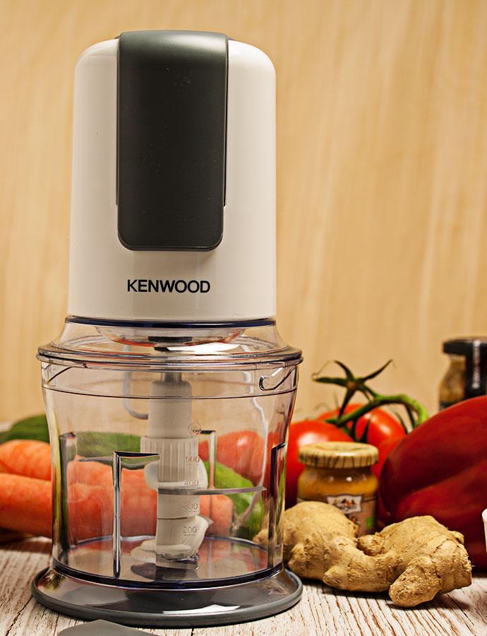 Vollständiger Kenwood CH580-Zerkleinerer mit 500-Watt und Quad-Blade-System in der Vollansicht. Gemüse im Hintergrund.