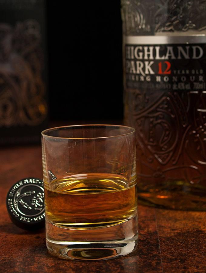 Zwei Finger hoch Highland Park Single Malt Scotch Whisky Viking Honour 12 Jahre in einem Whisky-Glas. Im Hintergund eine Flasche Highland Park Single Malt Scotch Whisky Viking Honour 12 Jahre und der Geschenkarton.