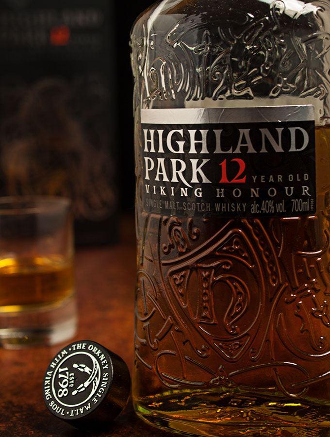 Nahaufnahme einer Flasche Highland Park Single Malt Scotch Whisky Viking Honour 12 Jahre mit Korken danebenliegend. im Hintergrund ein Glas Highland Park Single Malt Scotch Whisky Viking Honour 12 Jahre sowie die Geschenkverpackung.
